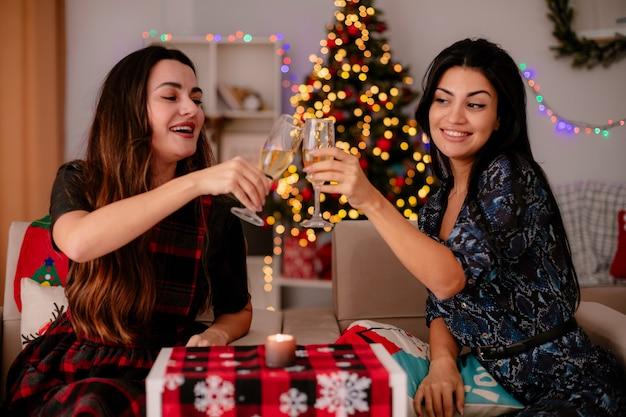 うれしそうなかわいい若い女の子がチャリンという音を立てて、アームチェアに座って家でクリスマスの時間を楽しんでいるシャンパンのグラスを見てください