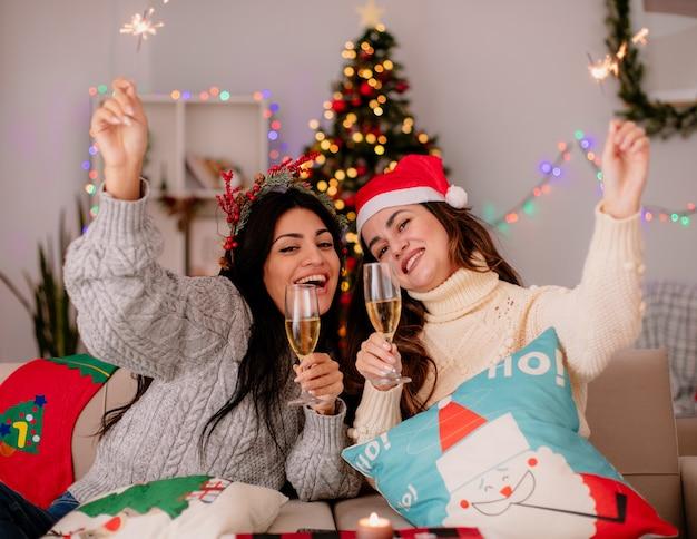 Gioiose ragazze carine tengono bicchieri di champagne e stelle filanti seduti sulle poltrone e godersi il periodo natalizio a casa