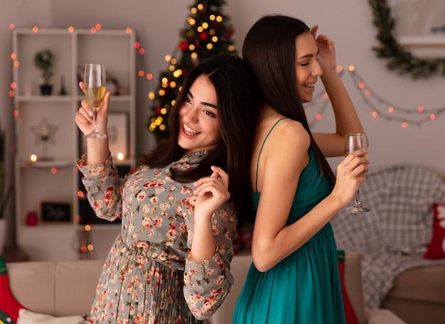 Gioiose e graziose ragazze stanno schiena contro schiena tenendo bicchieri di champagne godendosi il periodo natalizio a casa