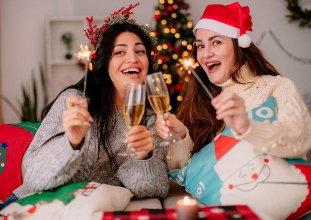 サンタの帽子をかぶった楽しいかわいい若い女の子はシャンパンのグラスをチリンと鳴らし、肘掛け椅子に座って家でクリスマスの時間を楽しんで線香花火を保持します
