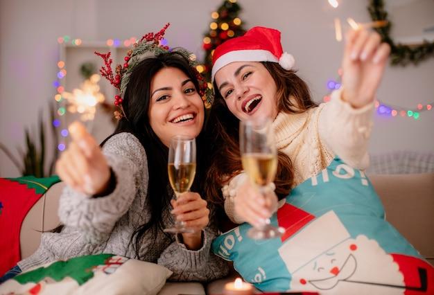 Gioiose belle ragazze con il cappello della santa tengono bicchieri di champagne e stelle filanti seduti sulle poltrone e godersi il periodo natalizio a casa