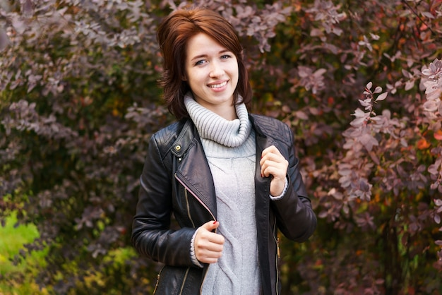 Joyful pretty young happy woman with a beautiful smile in a leather jacket and sweater posing in the...