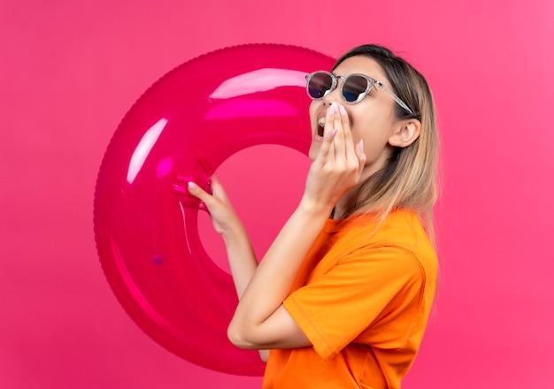 Una donna abbastanza giovane e gioiosa in una maglietta arancione che indossa occhiali da sole che chiama qualcuno mentre tiene l'anello gonfiabile rosa su una parete rosa