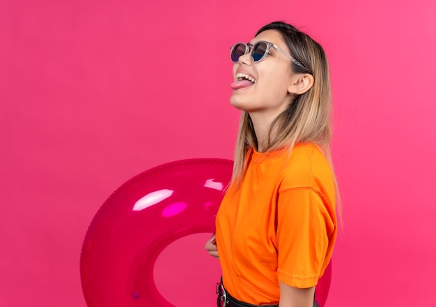 A joyful pretty young woman in an orange t-shirt wearing sunglasses showing her tongue while holding pink inflatable ring on a pink wall