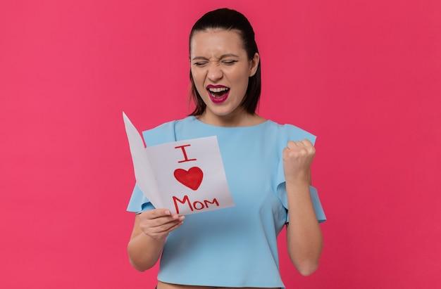 Gioiosa bella giovane donna che legge la lettera di suo figlio e tiene il pugno