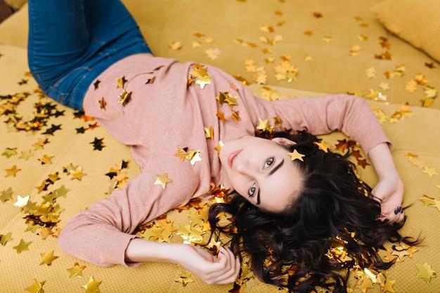 Радостная симпатичная молодая женщина с вьющимися волосами брюнет лежа на спине на бежевом диване в золотых мишурах. красивая модель выглядит, выражает настоящие эмоции, домашний уют