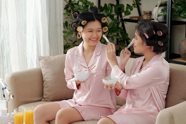 실크 잠옷을 입은 유쾌하고 예쁜 젊은 여성들은 각 얼굴에 클레이 마스크를 바르고 매끄럽게 ...