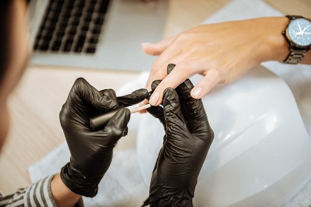 Радостный процесс. профессиональный опытный мастер по маникюру наслаждается процессом окрашивания ногтей для своей клиентки.