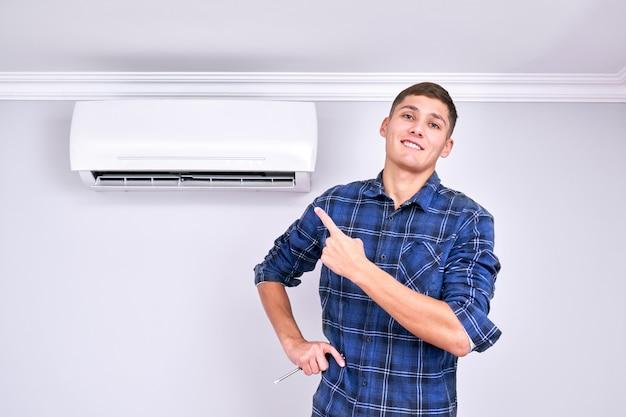 Радостный профессиональный ремонтник установил кондиционер в помещении, показывает пальцем и улыбается, хорошее обслуживание