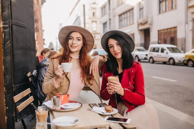 친구와 이야기하는 동안 차를 마시는 즐거운 나가서는 여자