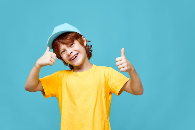 Joyful redhead boy in blue cap shows thumbs up yellow t-shirt smile blue background
