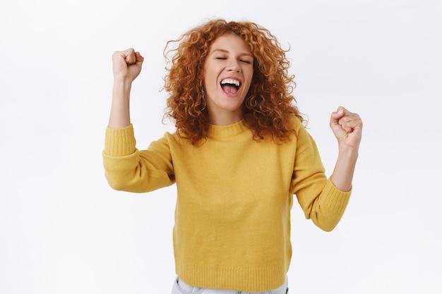 Радостная, рыжая кудрявая женщина празднует победу, чувствует себя удачливой и испытывает облегчение, кричит «да», добивается успеха, победы, торжествует, как закрытые глаза, поет от счастья и качает кулаком, белая стена