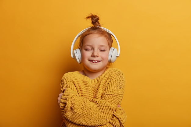 머리 롤빵을 가진 즐거운 빨간 머리 소녀는 자신을 포용하고 새 니트 스웨터에서 편안함을 느끼고 생생한 노란색 벽 위에 고립 된 스테레오 헤드폰으로 멜로디를 듣습니다. 어린이, 취미 개념