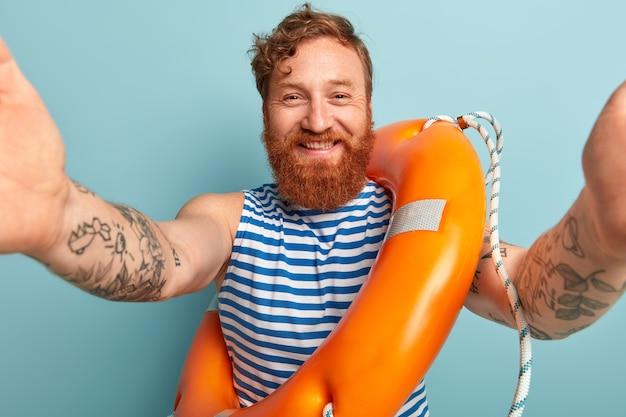 海で休暇中のうれしそうな赤毛の男は、自分撮りをします