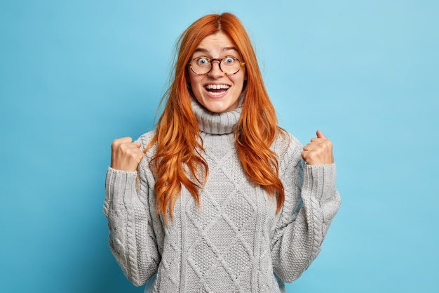Joyful redhead young woman with cheerful expression rejoices success clenches fists after achievement goals dressed in knitted grey sweater.