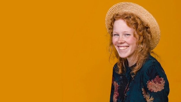 Joyful redheaded female in studio with colored background