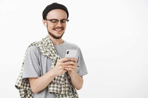 Радостный расслабленный и довольный молодой человек с бородой в очках и черной хипстерской шапке держит смартфон, улыбаясь на экран устройства, весело и интересно разговаривая через интернет