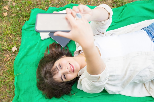 Joyful relaxed college girl shooting herself