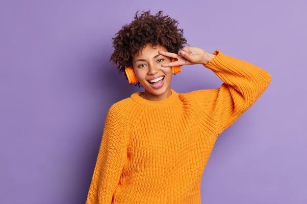 Joyful relaxed dark skinned millennial girl makes victory gesture listens favorite music in wireless headphones wears knitted orange jumper