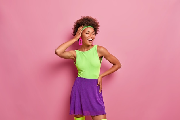Joyful relaxed dark skinned woman expresses happiness, closes eyes with pleasure, smiles broadly, keeps hand on head, wears bright summer outfit