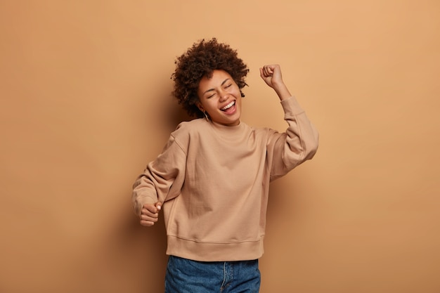 Joyful relaxed woman dances carefree against brown space, moves with rhythm of favourite music, feels pleased and delighted, wears brown jumper and jeans