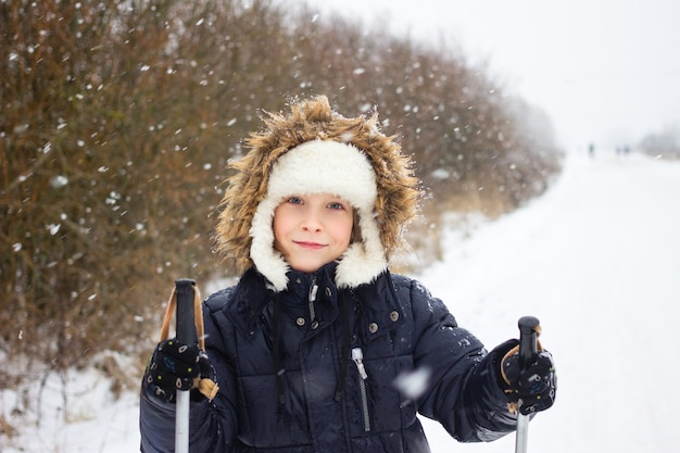 Joyful russian boy skiing in winter during snowfall with ski poles on forest road.