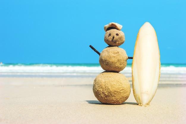 ターコイズブルーの海の水に対して砂の上にサーフボードを持ったうれしそうなサンドマンサーファー。熱帯のビーチでのクリスマスと新年のコンセプト。明るい色。サーフィンのコンセプト。