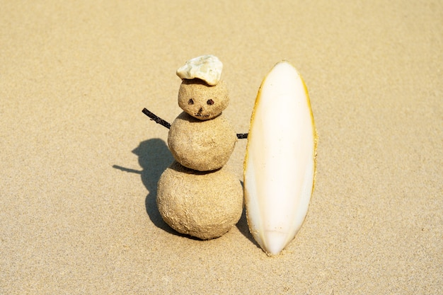 砂の上にサーフボードを持った楽しいサンドマンサーファー。熱帯のビーチでのクリスマスと新年のコンセプト。明るい色。サーフィンのコンセプト。ビーチの黄色い砂の帽子の砂の雪だるま。
