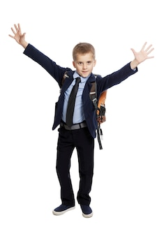 Joyful schoolboy in uniform with a backpack with his hands up.