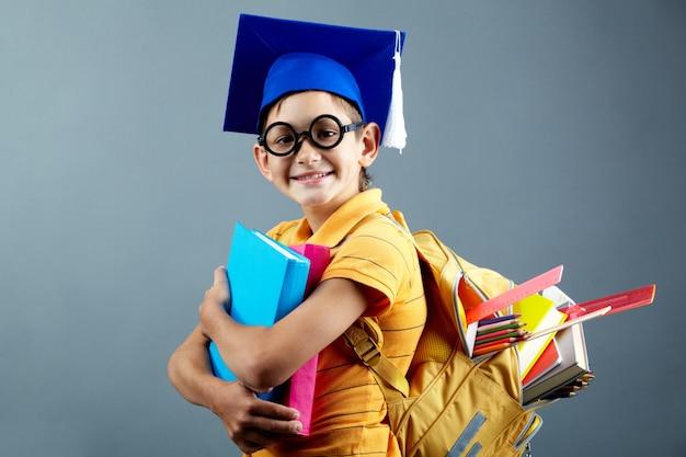 Радостный школьник с тяжелым рюкзаком