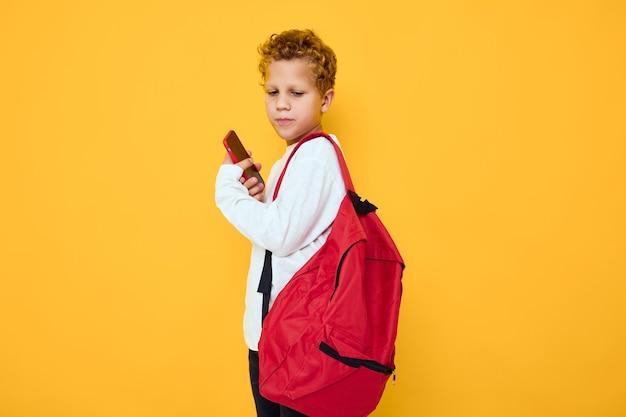 빨간 배낭을 메고 있는 즐거운 남학생이 전화 스튜디오 학습 개념을 부릅니다