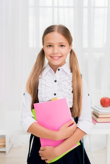 Joyful schoolgirl standing with bright workbooks