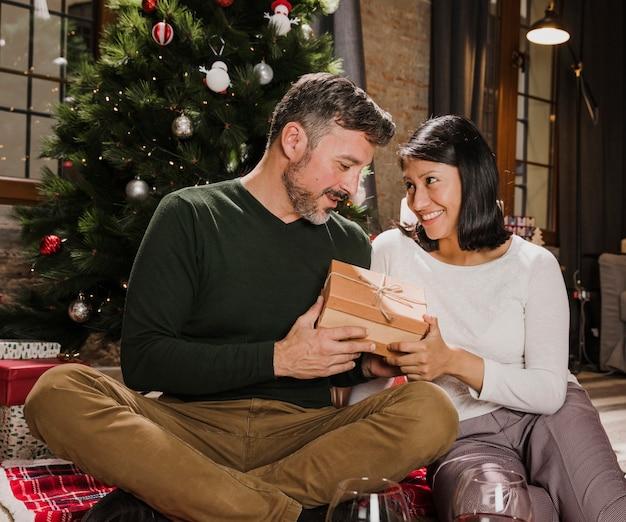 贈り物を交換するうれしそうな年配のカップル