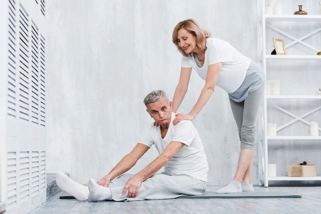 Joyful senior couple making fun while exercising at home