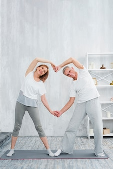 Joyful senior couple making heart shape with their hands while exercising at home