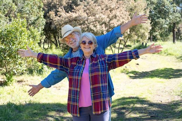 두 팔을 뻗은 숲에서 산책하는 즐거운 수석 부부. 건강한 라이프 스타일과 자연을 즐기는 두 행복한 은퇴 프리미엄 사진