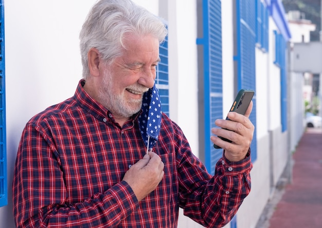 Joyful senior man takes off the protective face mask during a video call with his smart phone. white and blue background