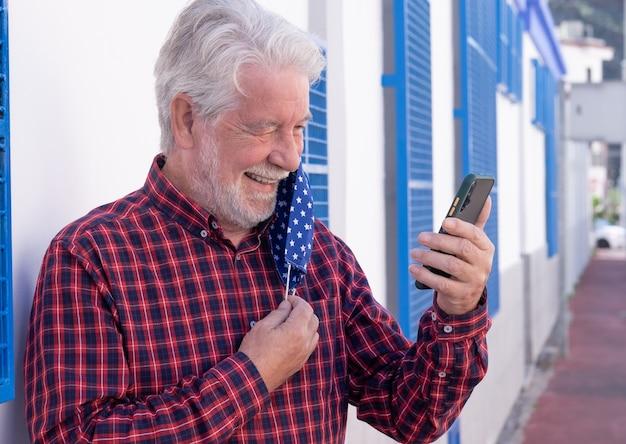 うれしそうな年配の男性がスマートフォンでビデオ通話中に保護マスクを外します。白と青の背景