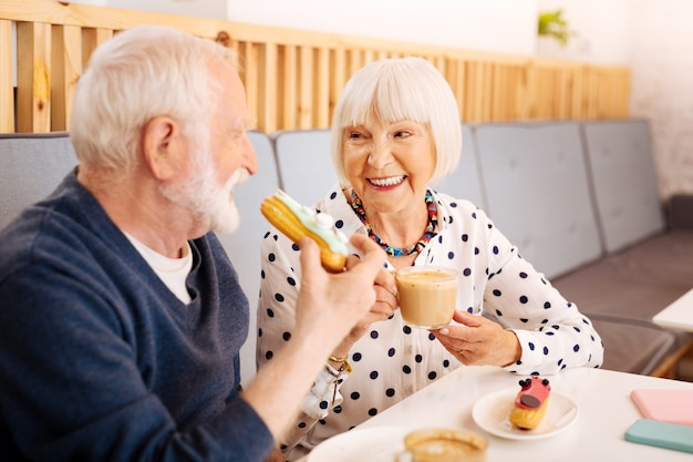 Радостная старшая женщина, наслаждающаяся кофе и старший мужчина, кусающий эклер