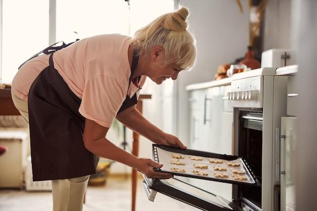 Радостная старшая женщина кладет поднос с печеньем в духовку