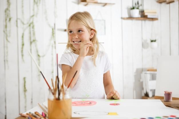 금발 머리와 주근깨 흰 옷을 입고 행복을 찾고 즐거운 7 살짜리 소녀.