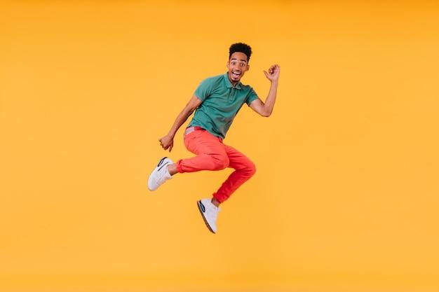 うれしそうな短い髪の男がジャンプします。楽しんでいる緑のtシャツの見事な男性モデルの屋内写真。
