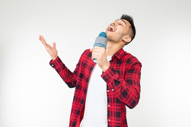 Радостный певец мужчина в рубашке улыбается и поет в микрофон