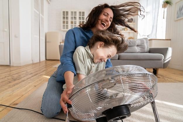 居間で風を吹くファンと一緒に家で一緒に興奮している息子と結合するうれしそうなシングルマザー