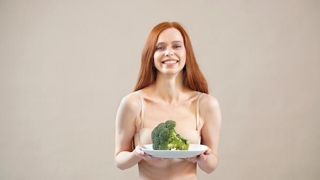 うれしそうなやせっぽちの女の子はブロッコリーを皿に保ち、適切な栄養を与え、過度の体重、食欲不振を恐れています