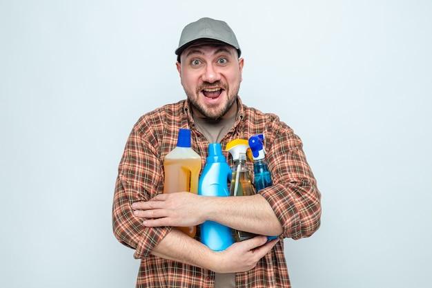 Gioioso uomo delle pulizie slavo che tiene in mano spray e liquidi per la pulizia