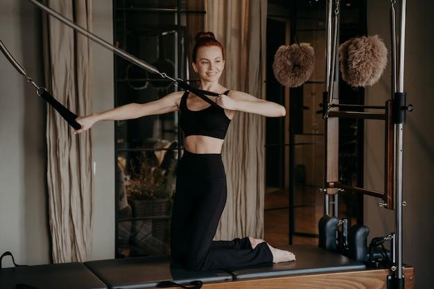 필라테스 개혁자에 즐거운 날씬한 생강 여자가 피트니스 스튜디오에서 훈련 세션 동안 팔 스트레칭 운동을 수행하고, 모든 움직임에 자신감을 보이고, 스포츠 옷을 입은 낚시를 좋아하는 여성