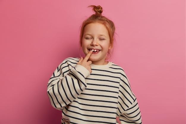 うれしそうな小さな赤毛の女性の子供は歯を指さし、目を閉じて幸せに笑い、お団子の結び目を持ち、ゆるい縞模様のセーターを着て、バラ色の壁に向かってポーズをとり、幼稚園に行く準備をします