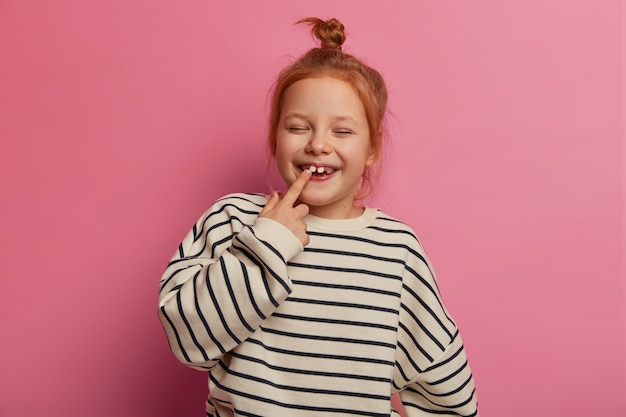 Joyful small redhaired female kid points at tooth, closes eyes and laughs happily, has bun knot, wears loose striped sweater, poses against rosy wall, prepares for going to kindergarten