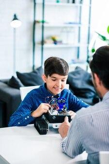 彼の父が彼を助けている間彼のロボットを構築するうれしそうな賢い少年